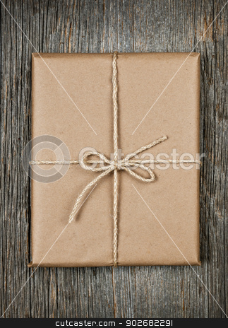Gift in brown paper tied with string stock photo, Gift package in brown paper wrapper tied with string on rustic wood background by Elena Elisseeva