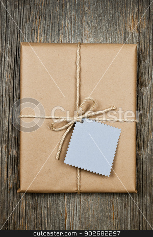 Gift with tag in brown paper stock photo, Gift package and card in brown paper wrapper tied with string on rustic wood background by Elena Elisseeva