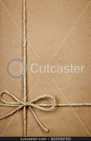 Package in brown paper tied with string stock photo, Brown paper gift package background with twine and copy space by Elena Elisseeva
