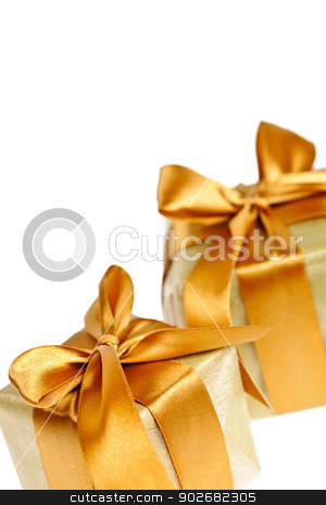 Two golden wrapped gift boxes stock photo, Two gift boxes in gold wrapping paper with ribbons and bows by Elena Elisseeva