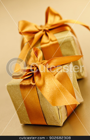 Two golden wrapped gift boxes stock photo, Two gift boxes in gold wrapping paper with ribbon and bow by Elena Elisseeva