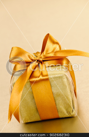Golden wrapped gift box stock photo, Gift box in gold wrapping paper with ribbon and bow by Elena Elisseeva