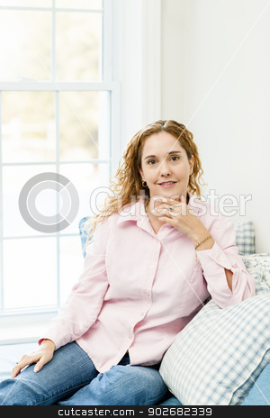Woman relaxing by the window stock photo, Smiling caucasian woman relaxing on couch by window by Elena Elisseeva