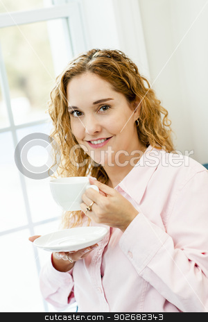 Woman relaxing by the window with beverage stock photo, Smiling caucasian woman relaxing by window holding cup of coffee by Elena Elisseeva