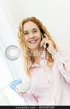 Woman talking on cordless phone stock photo, Smiling woman using cordless phone and drinking coffee by Elena Elisseeva