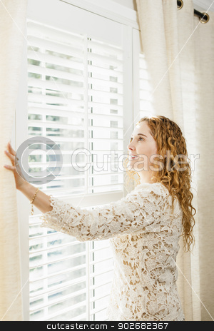 Smiling woman looking out window stock photo, Happy woman looking out big bright window with curtains and blinds by Elena Elisseeva