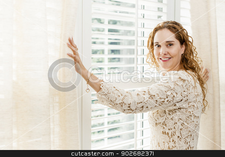 Smiling woman near window stock photo, Happy woman opening curtains on big sunny window with shutters by Elena Elisseeva