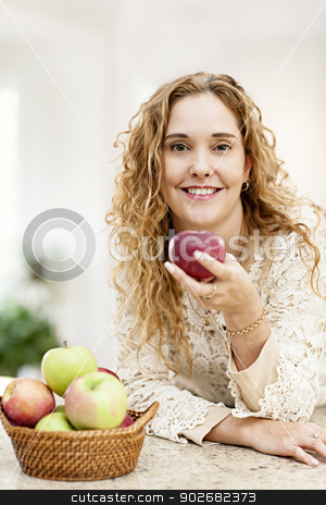 Smiling woman holding apple stock photo, Portrait of smiling woman holding red apple leaning on countertop in kitchen at home by Elena Elisseeva