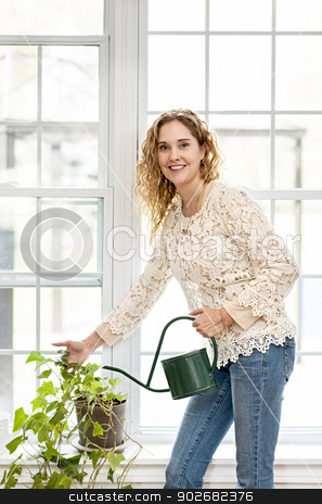 Smiling woman watering plant at home stock photo, Smiling woman watering green plant at home by window by Elena Elisseeva
