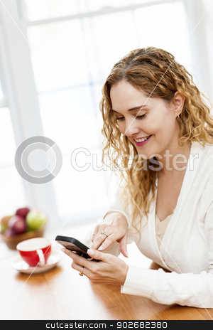 Smiling woman using smart phone stock photo, Portrait of smiling woman holding cell phone sitting at table in home kitchen by window by Elena Elisseeva