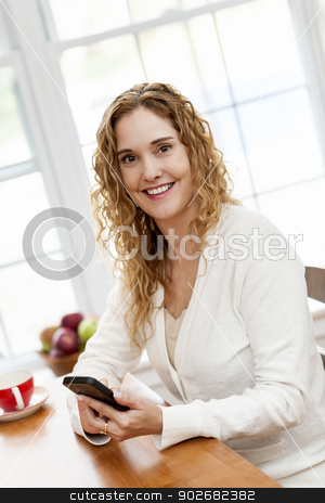 Smiling woman with smart phone stock photo, Portrait of smiling woman holding cell phone sitting at table in home kitchen by window by Elena Elisseeva