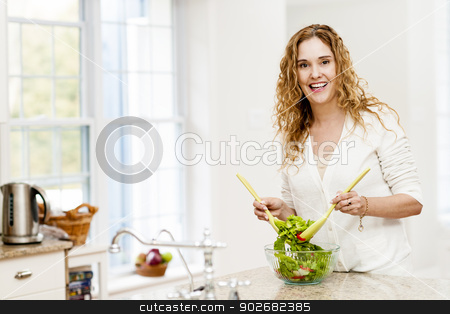 Smiling woman tossing salad in kitchen stock photo, Portrait of happy woman mixing salad in kitchen at home by Elena Elisseeva