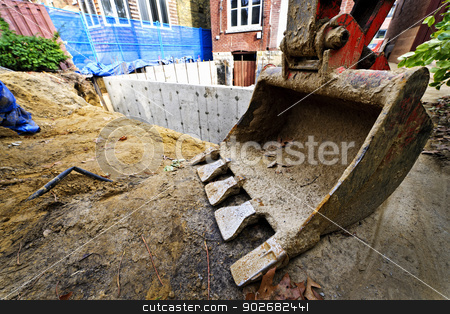 Building addition to home stock photo, Backhoe scoop at residential home renovation construction site by Elena Elisseeva