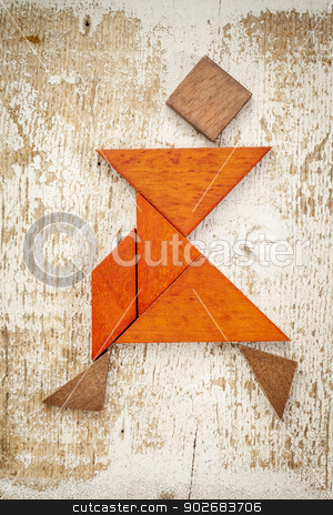 tangram dancer figure stock photo, abstract figure of a female dancer built from seven tangram wooden pieces, a traditional Chinese puzzle game; rough white painted barn wood background by Marek Uliasz