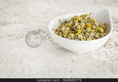 dried chamomile flowers stock photo, small ceramic bowl of  dried chamomile flowers against a ceramic tile background with a copy space by Marek Uliasz