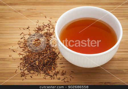 rooibos red tea  stock photo, rooibos red tea  -  a white cup of a drink and loose leaves on bamboo wood background, tea made from the South African red bush, naturally caffeine free by Marek Uliasz