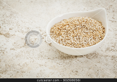 unhulled sesame seeds stock photo, small ceramic bowl of  unhulled sesame seeds against a ceramic tile background with a copy space by Marek Uliasz