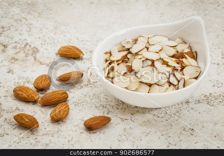 sliced raw almonds stock photo, small ceramic bowl of  sliced raw almonds against a ceramic tile background with a copy space by Marek Uliasz