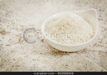 coconut flakes stock photo, small ceramic bowl of  coconut flakes against a ceramic tile background with a copy space by Marek Uliasz