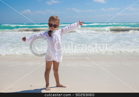 Beautiful little girl spread her arms standing at the white beach stock photo, Beautiful little girl spread her arms standing at the white beach by Dmitry Travnikov
