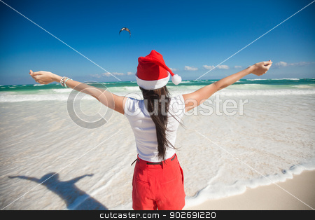 Back view of beautiful girl in santa hat walking like a bird on white beach stock photo, Back view of beautiful girl in santa hat walking like a bird on white beach by Dmitry Travnikov