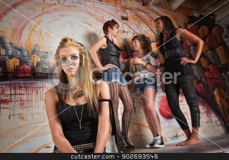 Shy Young Woman stock photo, Shy blond young woman near group of ladies talking by Scott Griessel