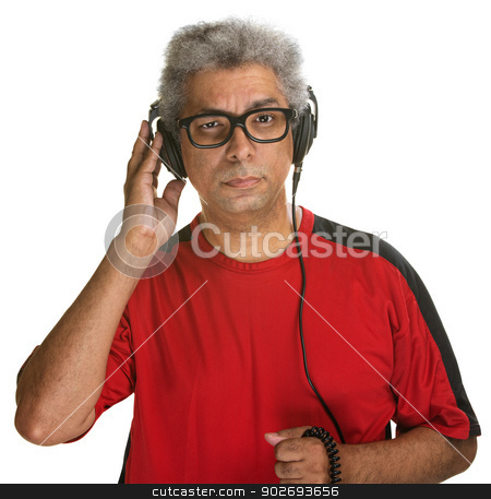 Serious Man Listening stock photo, Suspicious Hispanic male holding earphones on head by Scott Griessel