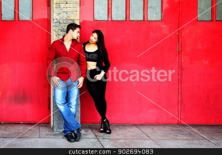 Young Couple Red Doors stock photo, Young couple in front of red fire station doors. by Henrik Lehnerer