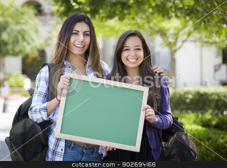 Mixed Race Female Students Holding Blank Chalkboard stock photo, Portrait of Two Attractive Mixed Race Female Students Holding Blank Chalkboard and Carrying Backpacks on School Campus. by Andy Dean
