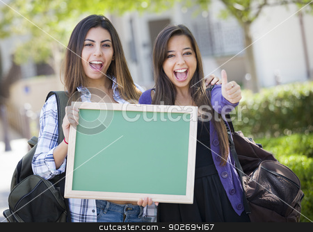 Mixed Race Female Students with Thumbs Up Holding Blank Chalkboa stock photo, Portrait of Two Attractive Mixed Race Female Students Holding Blank Chalkboard with Thumbs Up and Carrying Backpacks on School Campus. by Andy Dean