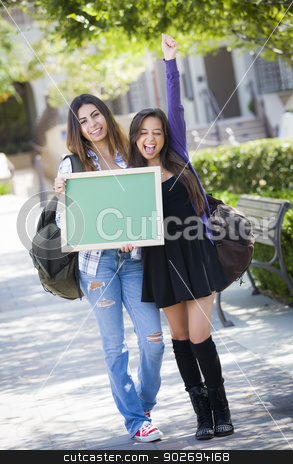 Excited Mixed Race Female Students Holding Blank Chalkboard stock photo, Portrait of Two Attractive Excited Mixed Race Female Students Holding Blank Chalkboard and Carrying Backpacks on School Campus. by Andy Dean