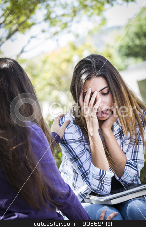 Stressed Sad Young Mixed Race Girl Being Comforted By Friend stock photo, Sad or Stressed Young Mixed Race Girl Being Comforted By Her Friend Outside on Bench. by Andy Dean