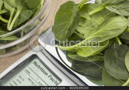 fresh spinach on diet scale stock photo, fresh spinach  on diet scale displaying nutrition facts - a diet concept by Marek Uliasz