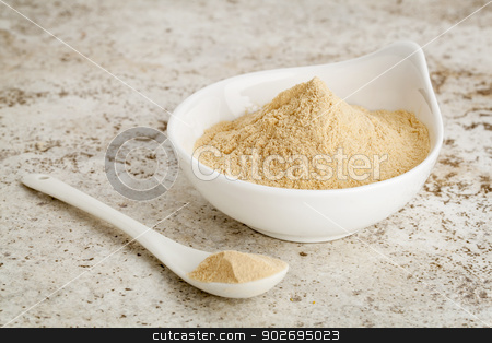 maca root powder stock photo, maca root powder - a small bowl with a spoon against ceramic tile surface by Marek Uliasz