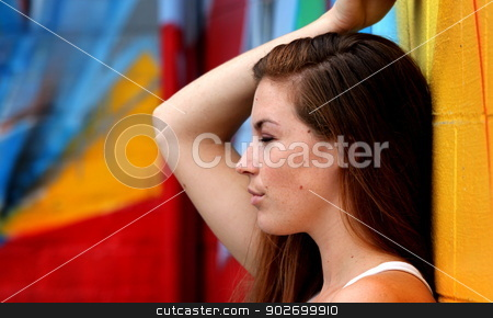 Portrait Of A Woman stock photo, Side view portrait of a woman with colorful wall in the background. by Henrik Lehnerer