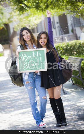 Mixed Race Female Students Holding Chalkboard With Back To Schoo stock photo, Excited Mixed Race Female Students Holding Chalkboard With Back To School Written on it. by Andy Dean