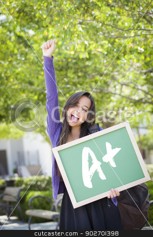 Mixed Race Female Student Holding Chalkboard With A+ Written stock photo, Excited Mixed Race Female Student Holding a Chalkboard With A+ Written on it. by Andy Dean