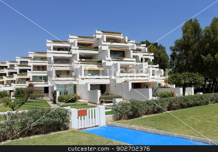 Spanish hotel apartments stock photo, Spanish hotel apartment complex with blue sky background. by Martin Crowdy