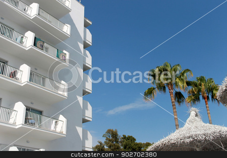 Spanish tourist hotel stock photo, White Spanish tourist hotel with palm trees and parasols, Majorca, Spain. by Martin Crowdy