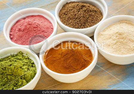 fruit and leaf powders stock photo, super fruit and leaf powders in small ceramic bowls - baobab, nori, yumberry, moringa, mangosteen by Marek Uliasz