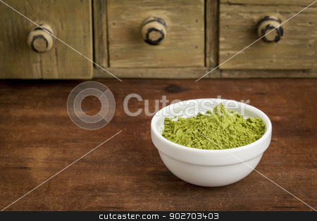 moringa leaf powder stock photo, moringa leaf powder in a small bowl with a rustic drawer cabinet by Marek Uliasz