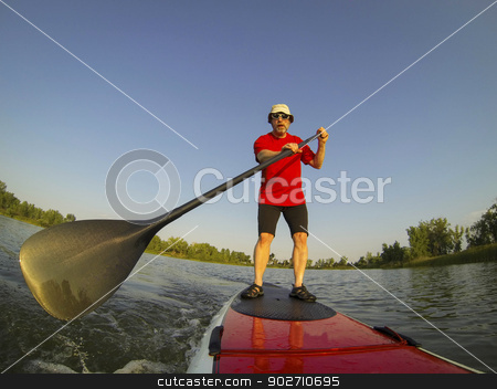 SUP - stand up paddling stock photo, mature male paddler enjoying workout on stand up paddleboard (SUP), calm lake in Colorado, summer, distorted wide angle view by Marek Uliasz