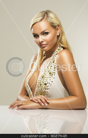 Beautiful glamorous blond woman stock photo, Beautiful glamorous busty blond woman with a lovely tan and serious enigmatic look wearing a stylish low cut dress with a plunging neckline sitting at a table, studio portrait of an exotic sexy woman by Instudio 68
