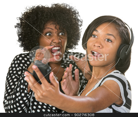 Mad at Loud Person stock photo, Annoyed middle aged lady near loud girl with headphones by Scott Griessel