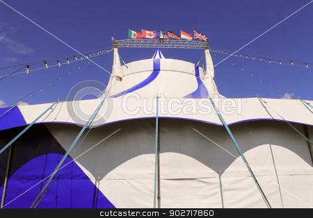 Blue and white circus tent stock photo, Blue and white circus tent with different country flags, blue sky and cloudscape background. by Martin Crowdy