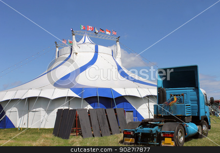 Circus tent and blue sky stock photo, Blue and white circus tent with articulated lorry in foreground. by Martin Crowdy