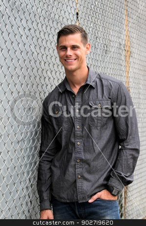 Portrait Of A Man stock photo, Portrait of a man standing in front of a chain link fence.   by Henrik Lehnerer