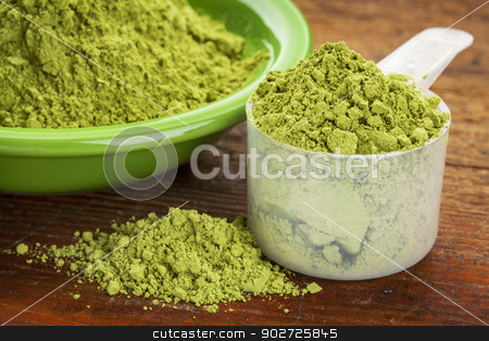 moringa leaf powder stock photo, measuring scoop of moringa leaf powder with a bowl on wooden surface by Marek Uliasz
