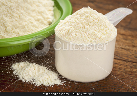 whey protein powder stock photo, measuring scoop of whey protein powder with a bowl on wooden surface by Marek Uliasz