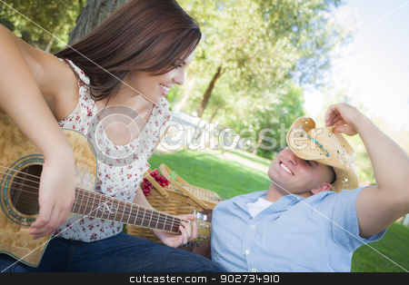 Mixed Race Couple with Guitar and Cowboy Hat in Park stock photo, Happy Attractive Mixed Race Couple with Guitar and Cowboy Hat in the Park. by Andy Dean